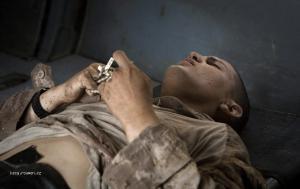 Foto tyzdna  Afganistan  Raneny americky vojak zviera v ruke ruzenec pocas osetrenia na palube helikoptery
