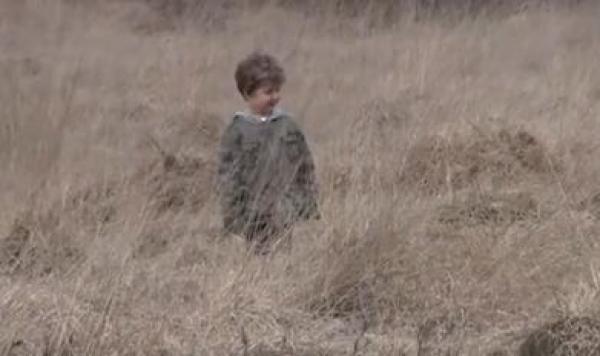 Opuštněný chlapec na louce