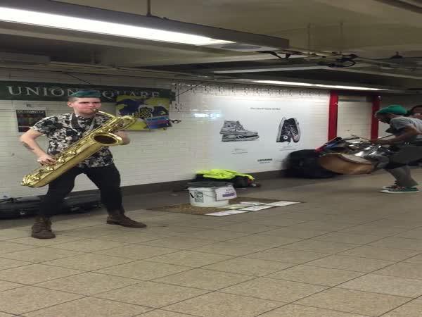 Muži hrají v metru